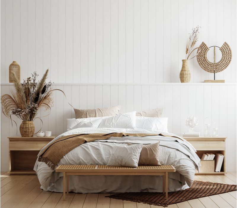 Coastal bedroom aesthetic idea with vertical white shiplap paneling, light wood floors, and natural wood accents
