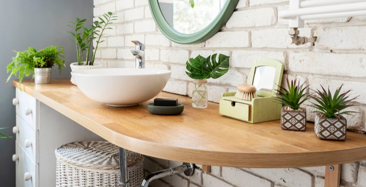 For a piece on bathroom counter decorations, a natural light wooden shelf sits mounted to a brick wall with a bunch of décor on it