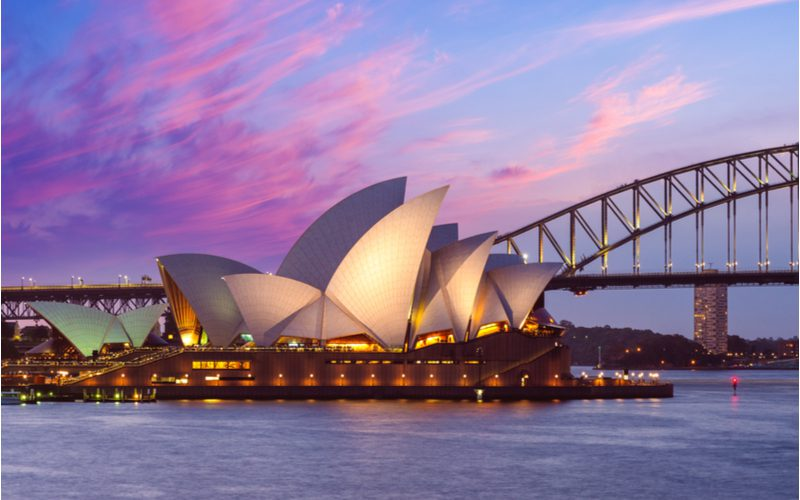 Close up of the Sydney Opera House at night overlooking the Sydney Harbour for a piece on famous buildings