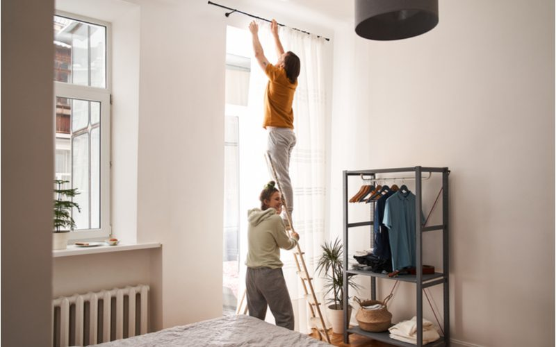 For a frequently asked section for a piece on should curtains touch the floor, a man hangs curtains while his partner supports the ladder