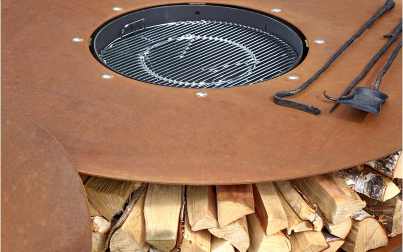 A wooden fire pit idea with wood storage shelves below the metal firepit on which sits a poker and ash shovel