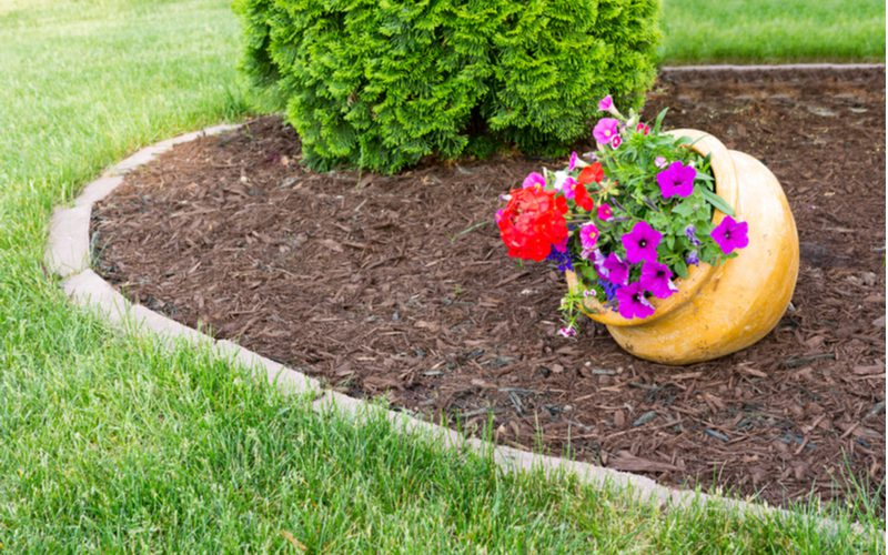 Piece on flower bed ideas with a yellow clay pot tipped over sitting in a simple mulch bed