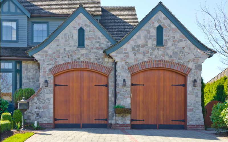 Medieval brick home with two brown garage doors pictured with a big porch overhang
