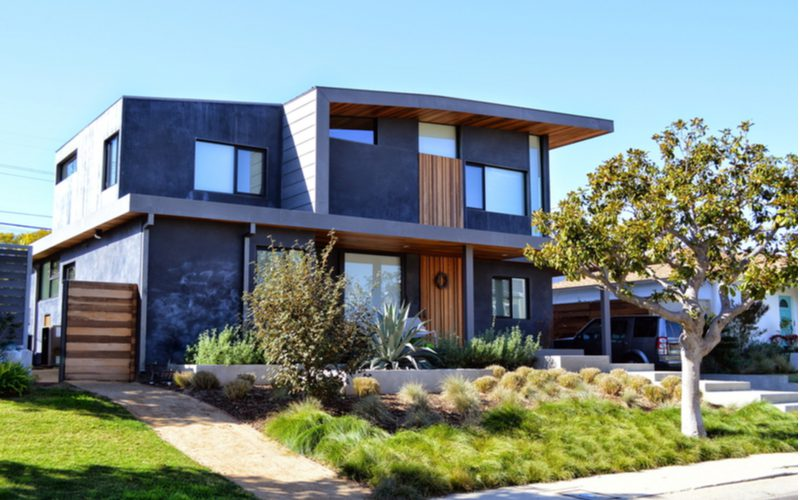 Modern box-style home that's dark grey in color with light brown fencing and wooding accenting for a piece on porch overhang and roof ideas