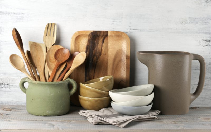 Natural wooden kitchen utensils and stone cookware sitting on a barnwood counter