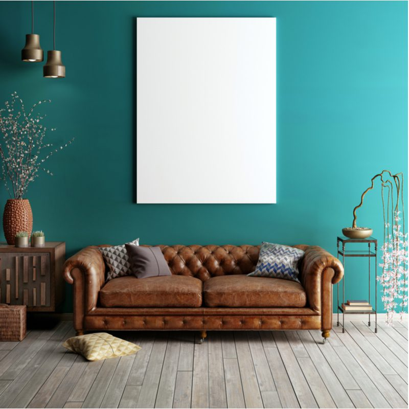 To help answer what color walls go with brown furniture, a nature-inspired living room with green wall, light grey flooring, and a plain white picture above the couch